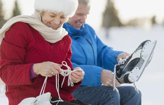 Uśmiechnięta para seniorów zakłada łyżwy